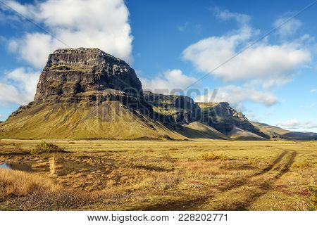 Scenic Landscape With Field Winding Car Tracks In Iceland