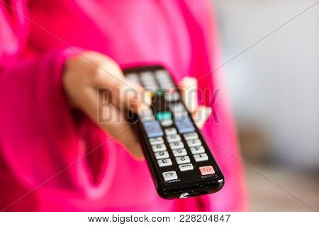 Tv Remote Control Held In Women's Hands. Switching Channels On The Tv With The Remote Control.