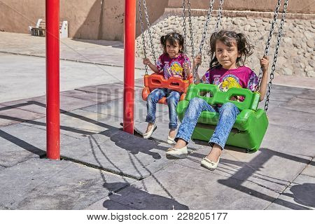 Kashan, Iran - April 26, 2017: Two Unknown Little Girls Twins, About 5 Years Old, Are Swinging On A