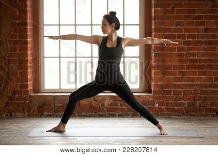 Young Sporty Woman Practicing Yoga, Doing Virabhadrasana 2 Exercise, Warrior Two Pose, Working Out,