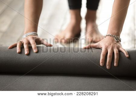 Hands Of Young Fitness Woman Unrolling Black Exercise Yoga Mat Before Working Out At Home In Living