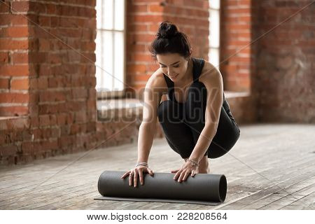 Attractive Happy Fit Young Woman Unfolding Black Yoga Or Fitness Mat Before Working Out In Loft Yoga