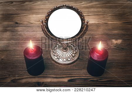 Golden Mirror (photo Frame) With Copy Space On The Magic Table Between A Two Burning Candles On Both