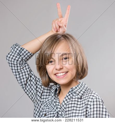 Emotional Portrait Of Attractive Caucasian Little Student Girl Up Two Fingers In Victory Sign Over H