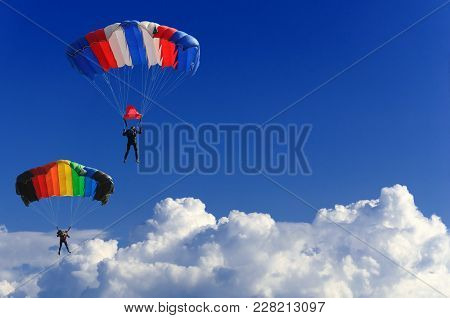 Two Parachutists Soar On Colorful Parachutes Across The Boundless Blue Sky Against The Background Of