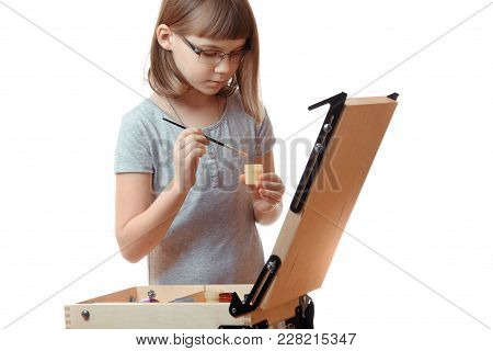 Horizontal Shot Of A Girl Teenager Painting On An Easel Isolated On White Background. Blonde Girl Wi