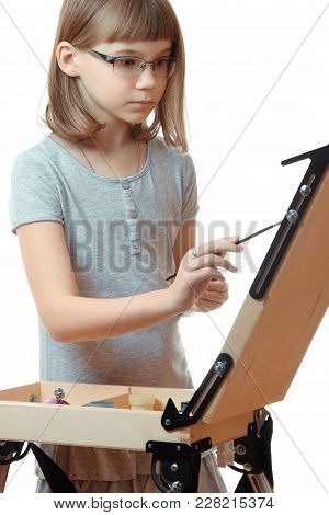 Vertical Shot Of A Girl Teenager Painting On An Easel Isolated On White Background. Blonde Girl With