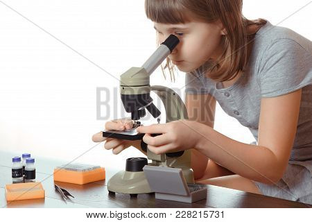 Horizontal Shot Of A Teen Girl In School Laboratory. Researcher Working With Microscope Isolated On