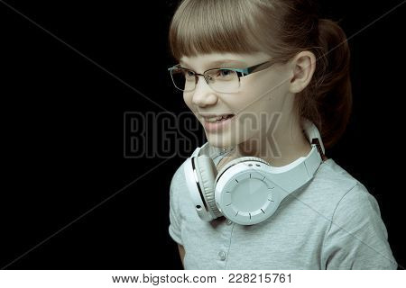 Horizontal Shot Of A Cheerful Teenager Girl In Glasses With White Headphones On Her Neck. The Concep