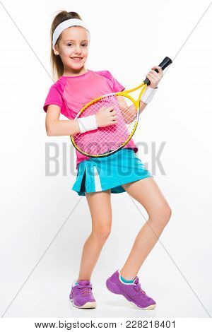 Adorable Smiling Little Girl In Sportswear Holding Tennis Racket In Her Hands Playing On Tennis Rack