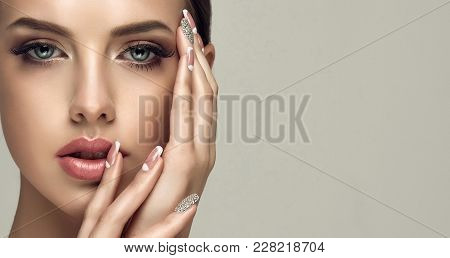Beautiful Model Girl With A Beige French Manicure Nail Design With Rhinestones . Fashion Makeup And
