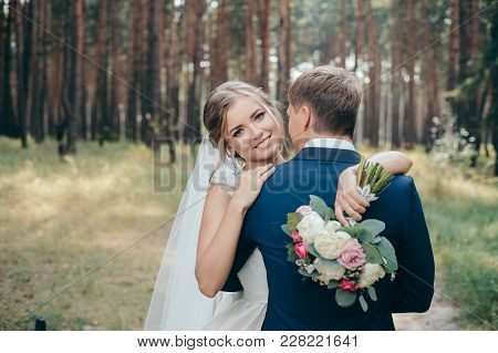 The Bride And Groom In Wedding Dresses On Natural Background.the Stunning Young Couple Is Incredibly