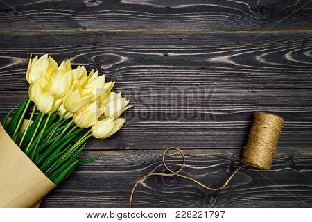 Spring Background With Bunch Of Yellow Tulip Flowers And Twine On Wooden Background, Copy Space. Fla