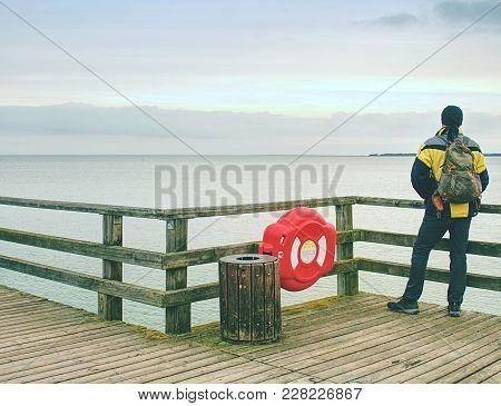 Man Thinking. Tourist  In Warm Clothes On Sea Mole At Wooden  Handrail. Autumn Misty Day. Tourist On