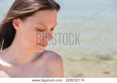 Closeup Portrait With Shoulders Of Brunette With Long Hair On The Beach. The Eyes Are Closed. Summer