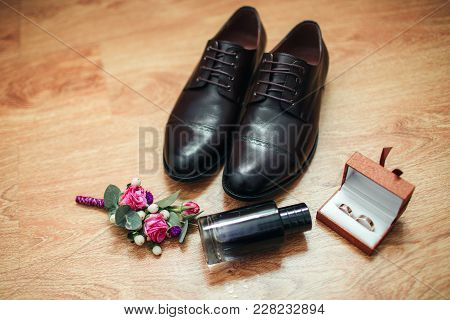 Men's Shoes Boutonniere And Perfume On The Background Of A Wooden Floor. Wedding Details.