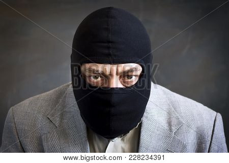 Businessman In A Balaclava On A Dark Background. Crime. Theft. Not An Honest Business