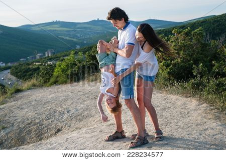 Family Photo In The Mountains Wearing Light Clothing. Son Hanging In Dad's Hands Upside Down.