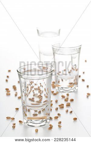 German Hard Liquor Korn Schnapps In Shot Glasses With Wheat Grains Over White Background