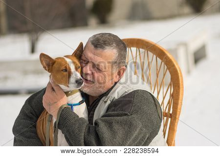 Portrait Of Caucasian Senior Man With His Cute Basenji Dog Sitting In Wicker Chair At Sunny Winter D