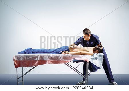 Chiropractic, Osteopathy, Dorsal Manipulation. Therapist Doing Healing Treatment On Women's Back . A