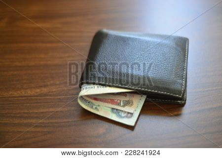 UAE Dirham currency notes popping out from a black leather wallet. Men's money purse on wooden background.