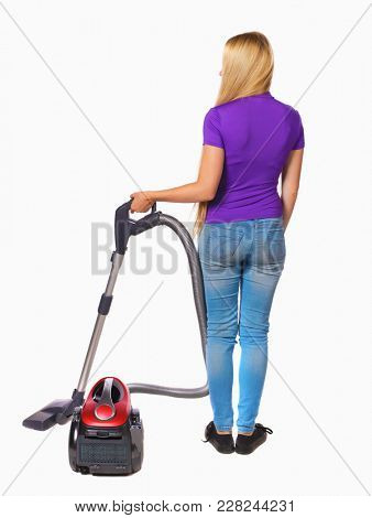 Rear view of a woman with a vacuum cleaner. She is busy cleaning. Rear view people collection.  backside view of person.   Long-haired blonde in the purple shirt holding a vacuum cleaner.