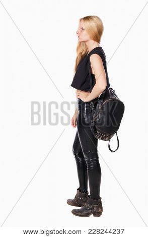 back view of standing young beautiful  woman.  girl  watching. Rear view people collection.  backside view of person.  Blonde in leather pants standing with a backpack resting sideways hand side.