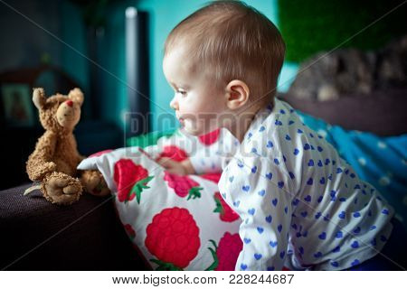 Lifestyle Portrait Of One Year Old Girl Looking At Her Little Teddy Bear