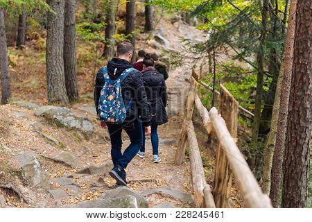 Man And Woman Walking Along Hiking Trail Path In Forest Wood