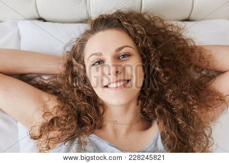 Top View Of Cheerful Young Female With Curly Bushy Hair Has Pleasant Smile As Lies On Comfortable Be