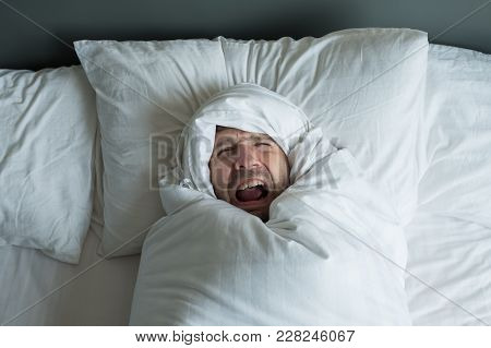 Caucasian Man Rolled In White Blanket. He Shouts Because Had Terrible Nightmare. Concept Of Problems