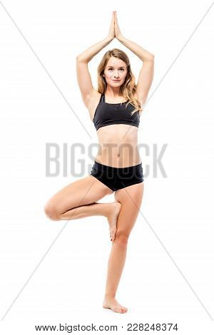 Woman In Black Sportswear Balancing On One Leg, Engaged In Yoga On A White Background