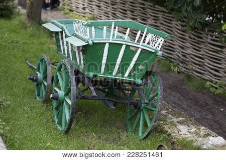 Green Wagon Horse. It Located On A Green Grass By Wattle Fence.