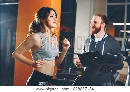 Coach Teaches Young Girl On The Treadmill. Coaching