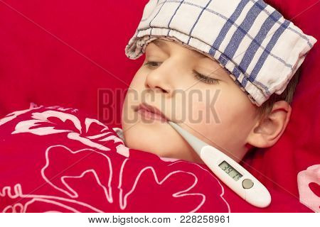 A Sick Boy Lying In Bed With A Thermometer In His Mouth