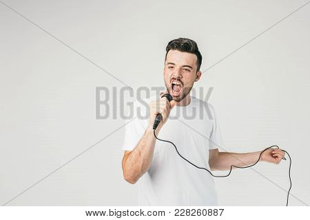 Another Picture Of A Guy In White T-shirt Holding A Mic In Right Hand And A Cord In His Left Hand An