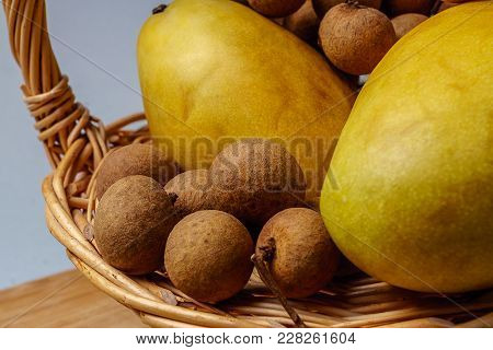 Tropical  Thai Ripe Fruit Mango And  Longan Fruit In A Basket Against Wooden Board, On Gray Backgrou