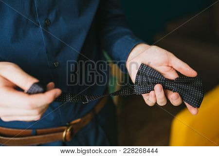 A Man In A Blue Shirt Is Holding A Bow Tie In Polka Dots. Wedding Stylish Accessory. Close Up