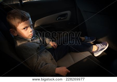 Sad Boy Sitting In The Back Seat Of A Car Looking In To The Camera