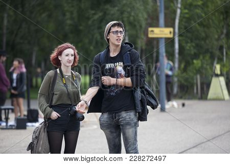 London, England - August 22, 2017 A Girl With A Camera And A Young Man With Glasses Listen To A Stre