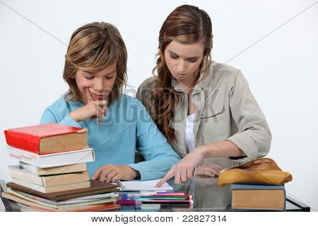 Sister helping her sibling with an assignment