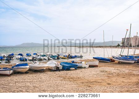 Boats And Small Motorboats On The Sand And In The Sea