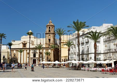 Cadiz, Spain - August 31, 2017: Tourists Relaxing At Pavement Cafes On Cathedral Square With The San