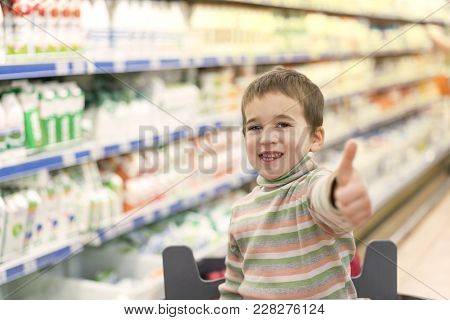 Happy Boy 4 Years In A Supermarket On The Background Of Shelves With Milk And Yogurt. Sun Rays.