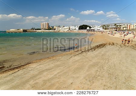 People Relaxing On Caleta Beach, One Of The Most Beautiful In Cadiz, With Santa Catalina Castle At T
