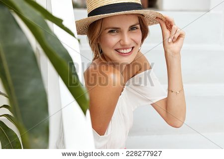Sideways Portrait Of Pleased Happy Woman Wears Summer Straw Hat, Demonstrates Bare Shoulders, Sits I