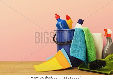 Variety Of House Cleaning Products On Wood Table, Closeup. Bucket, Brush, Colourful Rags, Disinfecti