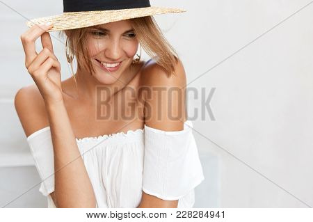 Dreamy Happy Young Woman In Straw Hat, Poses Alone With Cheerful Expression, Looks Thoughtfully Down