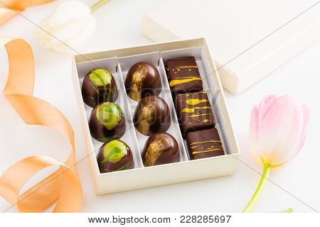 Assortment Of Luxury Bonbons In Gift Box On White Background With Flowers. Exclusive Handmade Chocol